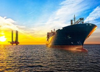 Oil tanker at sea, platform in background